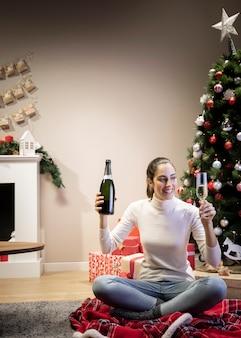 Bella donna che tiene una bottiglia e un bicchiere di champagne