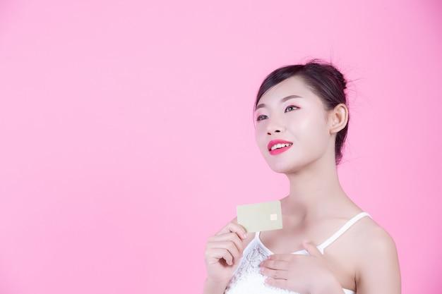 Bella donna che tiene una carta su uno sfondo rosa.