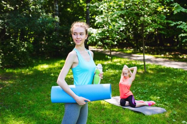 Bella donna che tiene una stuoia e una bottiglia di acqua di yoga.