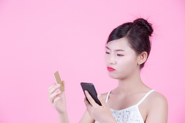 Bella donna che tiene uno smartphone e una carta su uno sfondo rosa