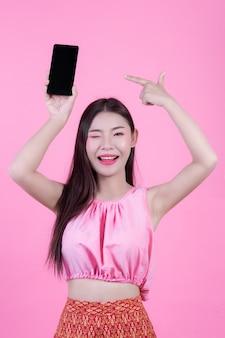 Bella donna che tiene uno smartphone su uno sfondo rosa.