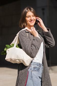Bella donna che trasporta verdure biologiche