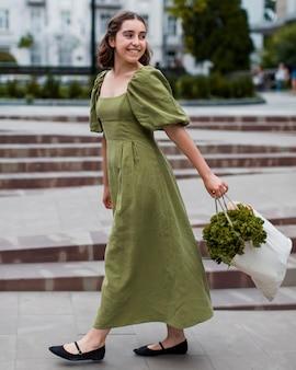 Bella donna che trasportano generi alimentari biologici