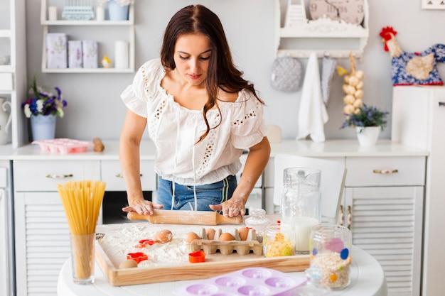 Bella donna che usando il rullo della cucina