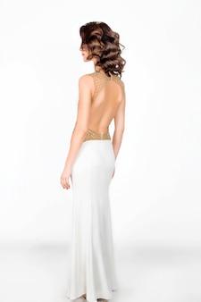 Bella donna chic in abito lungo bianco con schiena aperta