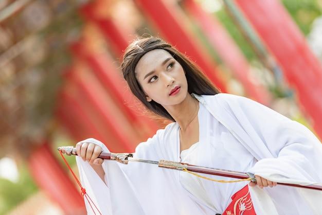 Bella donna cinese con un abito tradizionale con una spada affilata nelle sue mani.