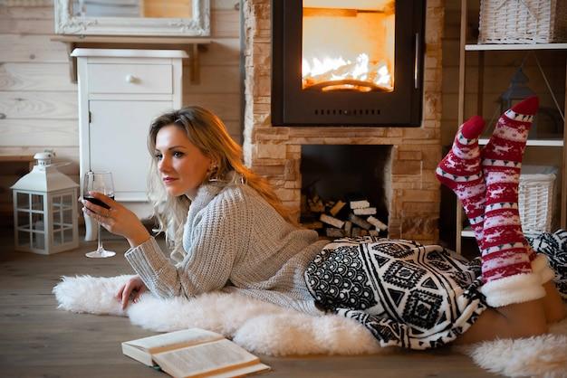 Bella donna con bicchiere di vino e libro rilassante nella baita di montagna rustica