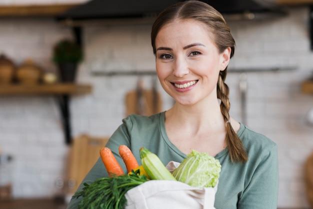 Bella donna con borsa con verdure biologiche