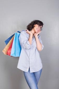 Bella donna con borse della spesa alle spalle