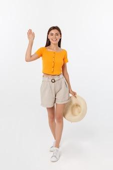 Bella donna con camicetta arancione dicendo ciao
