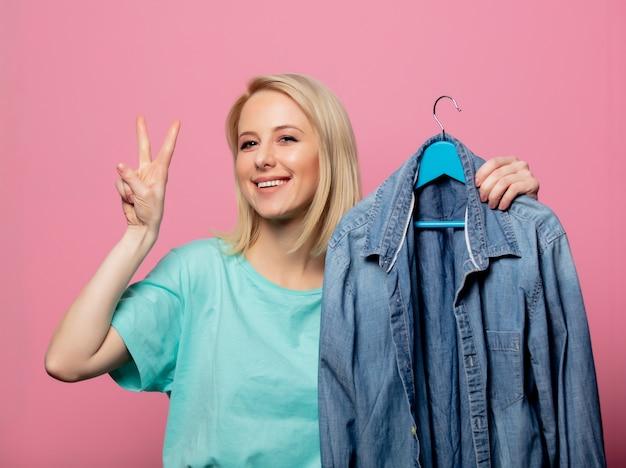 Bella donna con camicia su un gancio sul muro rosa