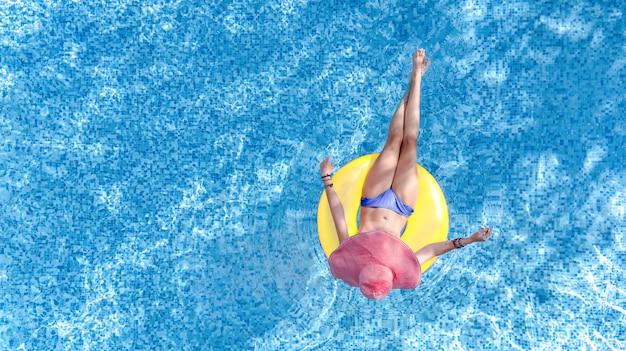 Bella donna con cappello in piscina vista aerea dall'alto, ragazza in bikini si rilassa e nuota sulla ciambella ad anello gonfiabile e si diverte in acqua in vacanza con la famiglia, località di villeggiatura tropicale