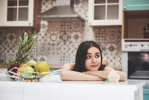 Bella donna con cibo sano frutta in cucina.