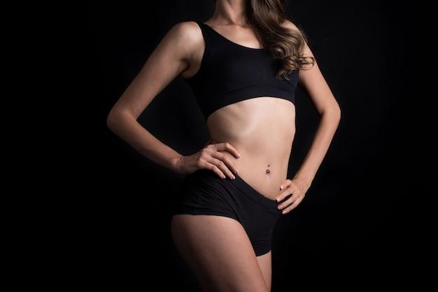 Bella donna con corpo sano su sfondo nero