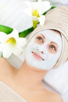 Bella donna con crema sul viso in una spa