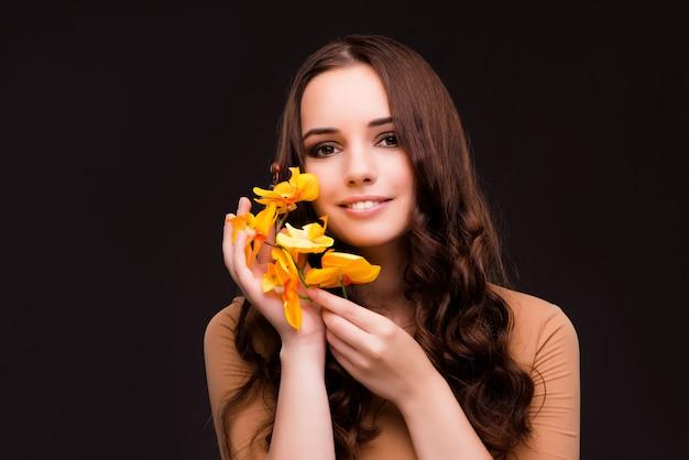 Bella donna con fiore orchidea isolato su fondo nero