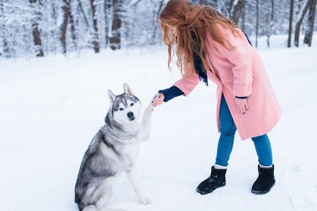 Bella donna con giocoso cane husky