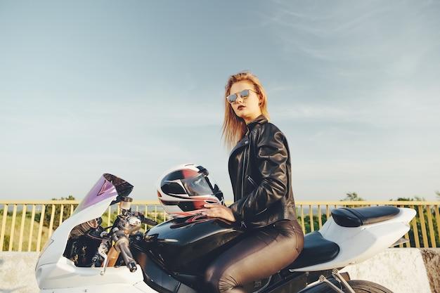Bella donna con gli occhiali da sole guida su una moto