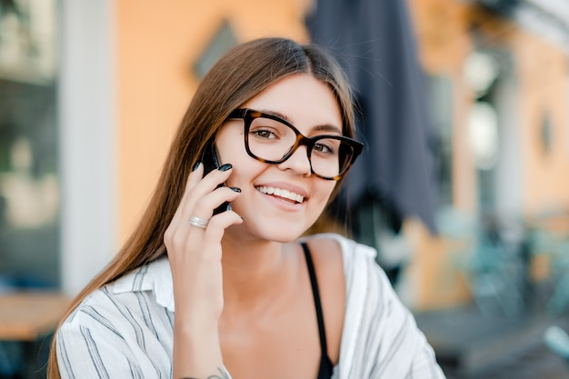 Bella donna con gli occhiali parla al telefono