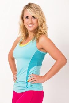 Bella donna con i capelli biondi e in abiti di allenamento sta lavorando su uno sfondo bianco