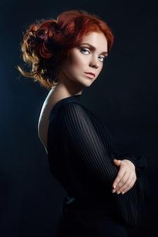Bella donna con i capelli rossi sul nero
