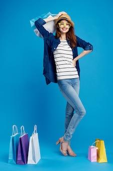 Bella donna con i pacchetti nelle mani n shopping consumo lifestyle blu