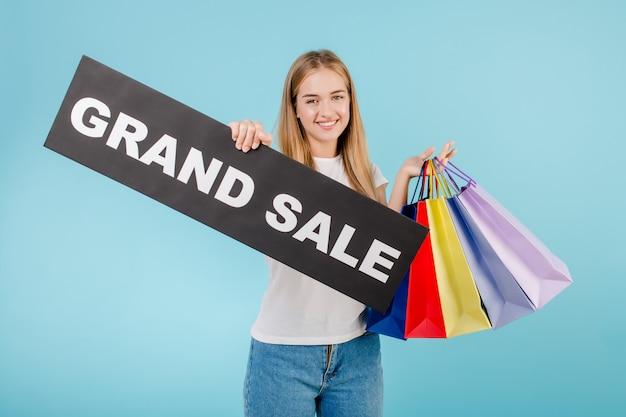 Bella donna con il grande segno di vendita e sacchetti della spesa variopinti isolati sopra il blu