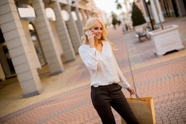 Bella donna con il sacchetto della spesa di carta a piedi dai negozi