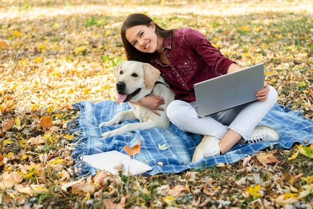 Bella donna con il suo cagnolino nel parco