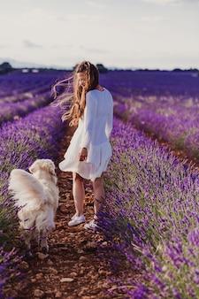 Bella donna con il suo cane golden retriever nei campi di lavanda al tramonto.
