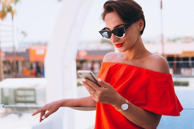 Bella donna con il telefono in vacanza