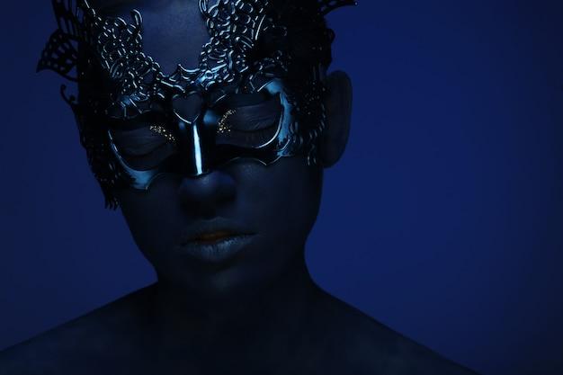 Bella donna con la faccia blu con maschera
