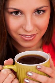 Bella donna con la tazza a casa