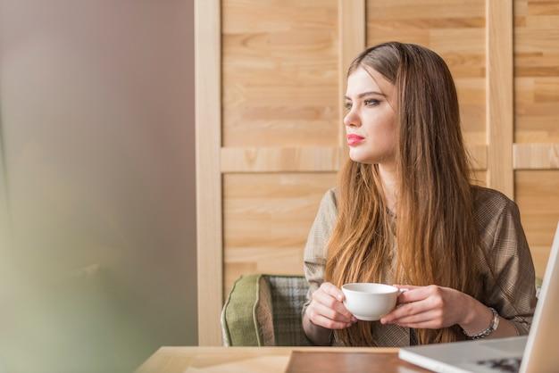 Bella donna con la tazza di tè guardando al lato
