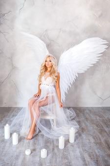 Bella donna con le ali bianche su sfondo bianco