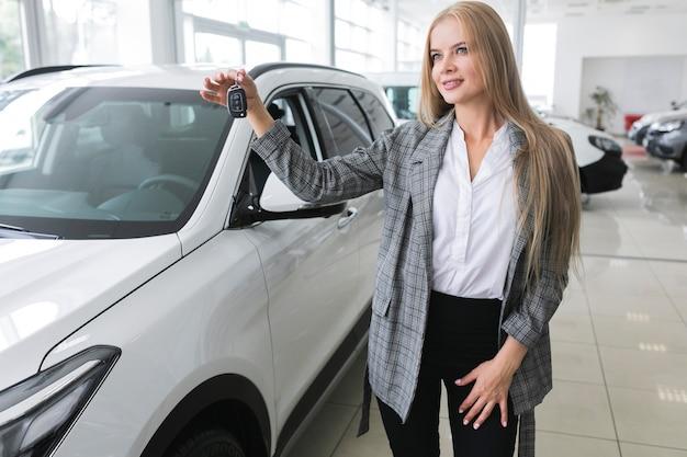 Bella donna con le chiavi della macchina guardando lontano