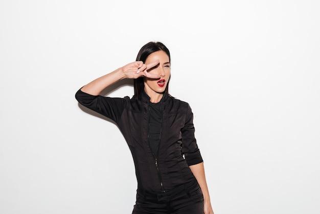 Bella donna con le labbra rosse che mostra il gesto di pace.