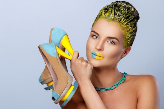 Bella donna con le scarpe variopinte della tenuta gialla