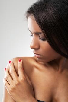 Bella donna con le spalle nude sta toccando la spalla