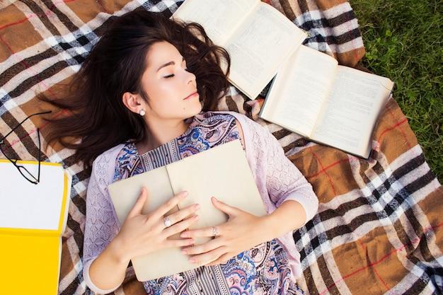 Bella donna con libri nel parco