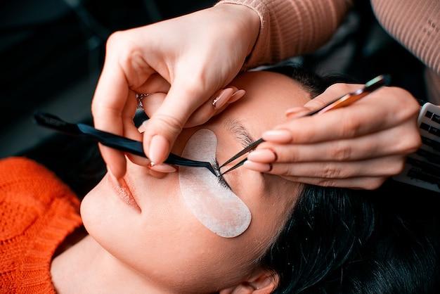 Bella donna con lunghe ciglia in un salone di bellezza. procedura per l'estensione delle ciglia. le ciglia si chiudono
