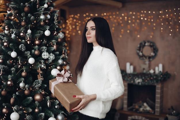 Bella donna con lunghi capelli scuri in maglione bianco detiene il regalo di natale