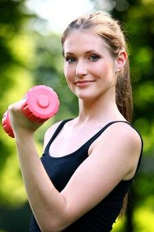 Bella donna con manubri rosa nel parco