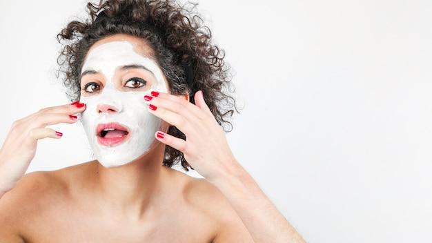 Bella donna con maschera facciale isolato su sfondo bianco