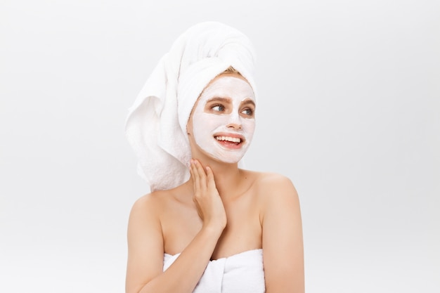 Bella donna con maschera facciale su sfondo bianco