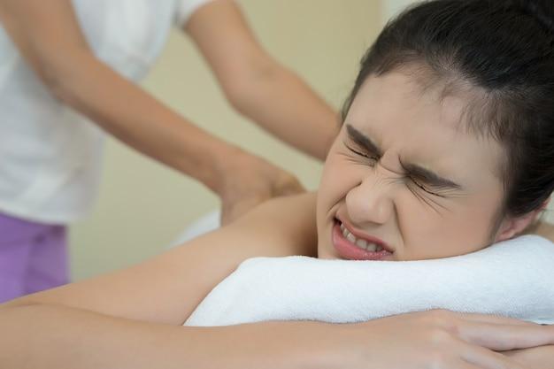 Bella donna con massaggio alla schiena e sentirsi visibilmente bene.