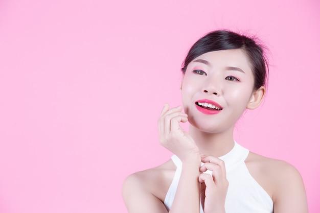 Bella donna con pelle sana e bellezza su uno sfondo rosa.