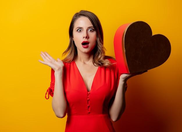 Bella donna con scatola a forma di cuore sulla parete gialla