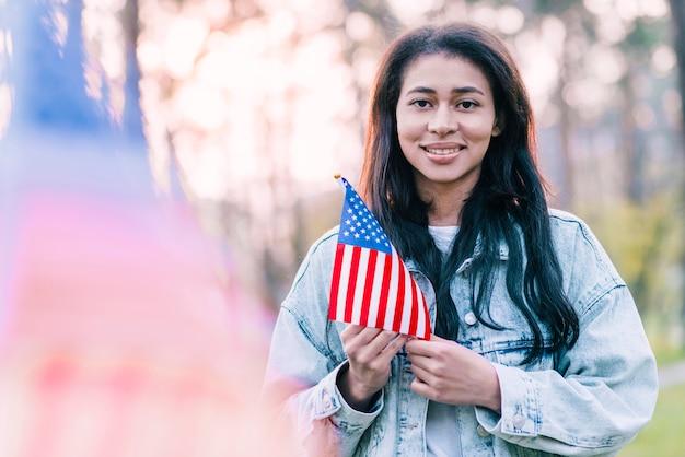 Bella donna con souvenir bandiera americana all'aperto