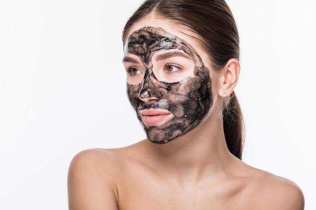 Bella donna con un'argilla o una maschera di fango sul suo viso isolato sul muro bianco